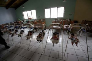 Children sit in bouncing chairs at the Casa Quivira children's home