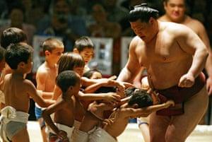 Boys push a professional sumo wrestler