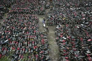 Workers prepare to destroy illegal motorbikes