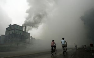 Cyclists ride through thick pollution produced by a nearby factory