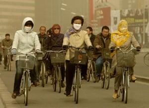 Women wearing masks while riding bikes