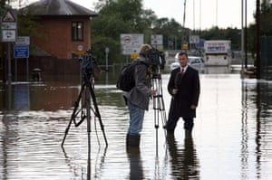 :  A TV camera crew report in a flooded street in Tewkesbury