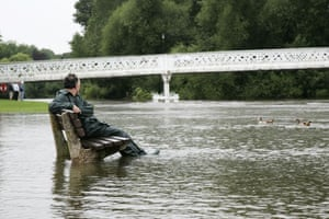 A man sits on a partly submerged bench