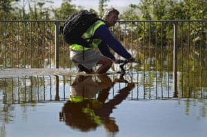 A cyclist tackles flood waters as they begin to recede in Tewkesbury