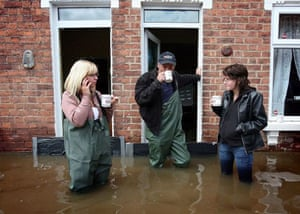 Coyeta Brown, Claus Pittaway and Sophie Pittaway have a cup of tea in flooded Alney Terrace