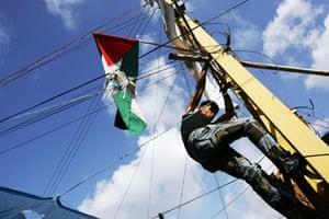 A man fixes a Palestinian flag on an electricity pole