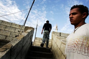 Saleh, a secular young man, stands at the stairs of his house