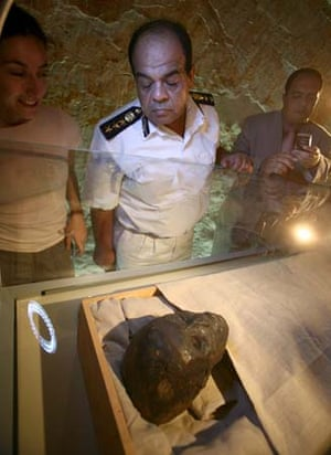 A military officer inspects the mummy
