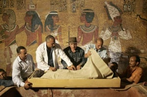 Workers unwrap the mummy
