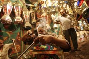 A man makes a 'fanous ramadan', a traditional candle lamp
