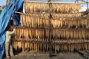 A man supervises the drying of raw vermicilli