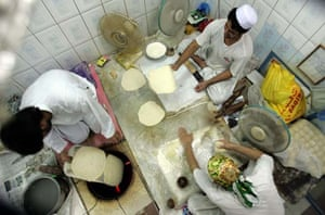 Afghani bakers living in Dubai make bread in a traditional oven