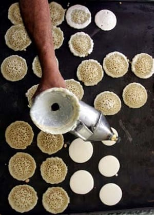 A Palestinian baker makes small traditional pancakes