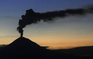 Popocatepetl is seen spewing smoke and ash at sunset