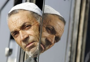 A Kashmiri Hajj pilgrim looks from bus window before they depart for Mecca