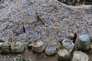 Wuhan, China: A worker amidst plastic bottles at a recycling plant