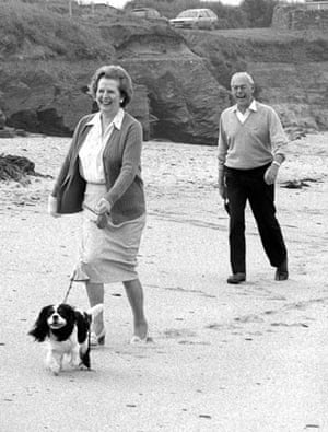 1986, Cornwall, UK: Margaret Thatcher and husband Denis take their holiday host's King Chales Spaniel for a walk along the beach at Constantine Bay