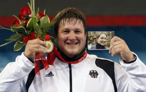 Matthias Steiner of Germany holds a photo of his late wife Susann as he poses with his gold medal