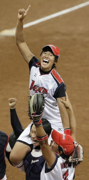 Japan team lifts pitcher Yukiko Ueno while celebrating winning the gold medal against the USA