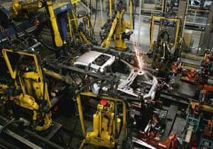 Industrial robots assemble a car at Shanghai General Motors factory