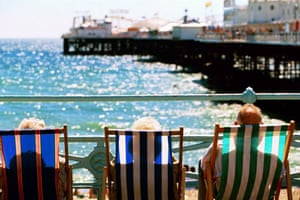 Brighton, UK: An elderly couple relaxing in deckchairs by the pier