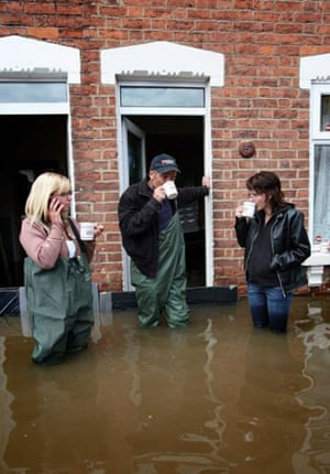 Coyeta Brown, Claus Pittaway and Sophie Pittaway have a cup of tea in flooded Alney Terrace in Gloucester