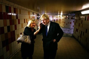 London Mayoral candidate Boris Johnson takes a phone call from a voter during a campaign walk through a subway in Gant's Hill
