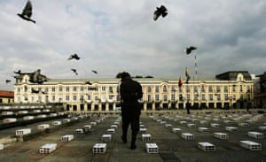 A police officer looks at bricks with the names of the victims of violence in Colombia written on them at Bolivar square