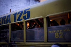 A woman looks out from a public bus in Guatemale City