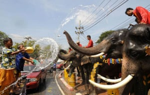 Children enjoy a water fight with elephants during the Thai New Year festival