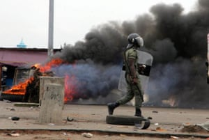 A police officer walks past a burning road block in Port Bouet, Ivory Coast