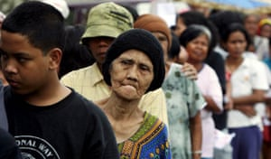 Poor people queue in a line to get a free one kilo bag of rice in Indonesia