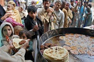People queue to get free food from a restaurant in Rawalpindi, Pakistan
