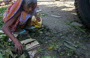 An elderly woman picks through rubbish beneath a truck carrying food for anything edible in Bangladesh