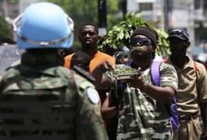 A demonstrator eats grass in front of a U.N. Brazilian peacekeeping soldier in Port-au-Prince, Haiti
