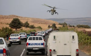 Russian attack helicopter hovers over a convoy of Georgian police and international journalists