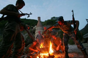 Abkhaz fighters cook food outside the town of Chkhalta
