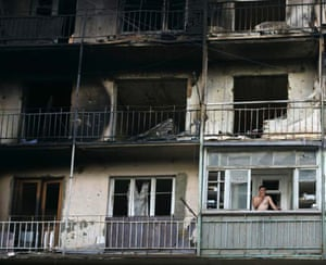 Tskhinval, South Ossetia: An local man smokes a cigarette as he stands on the balcony of a ruined apartment block