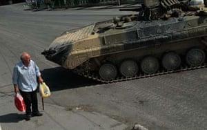 A man in the centre of Gori near a tank