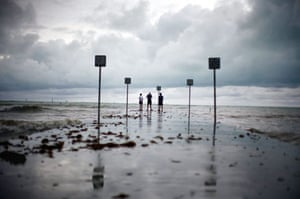 Key West, US: Residents stand at the end of a pier during a lull in tropical storm Fay