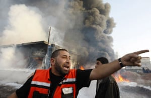 A Palestinian firefighter shouts in front of a burning building following an Israeli air strike in the Gaza Strip