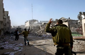 Palestinian Hamas security guards inspect the scene after an Israeli missile attack in the streets of Gaza City