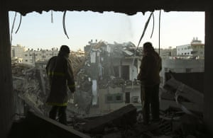 Palestinians inspect the building of Hamas TV destroyed following an air strike