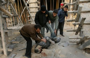 Palestinians inspect the body of a man following an Israeli air strike near Al-Shifa mosque in Gaza City