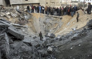 Palestinians gather in the crater of an Israeli missile strike on a building used by Hamas in Gaza City