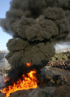 Palestinian firefighters attempt to douse flames at the site of an Israeli air strike in Rafah