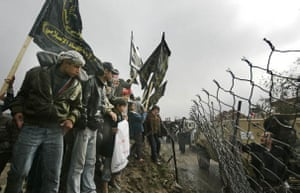 Palestinians stand on the Egypt-Gaza border during an Islamic Jihad demonstration