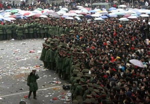 Soliders hold back passengers gathered outside the railway station in Guangzhou