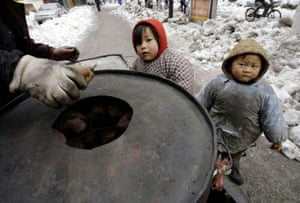 Two local children look at a sweet potato vendor in Nanjing
