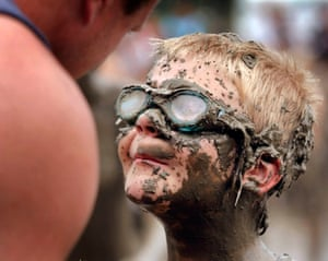 Michigan, US: Danny Sullivan, eight, with his father at the annual Mud Day celebration in Westland. The event consists of 200 tons of topsoil mixed with 20,000 gallons of water and about 1,000 children. Photograph: Bill Pugliano/Getty Images
